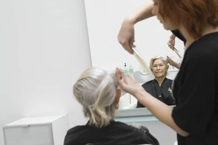 Senior woman getting haircut from female hairdresser in salon