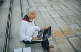 Business woman using laptop outdoors while sitting on the stairs.