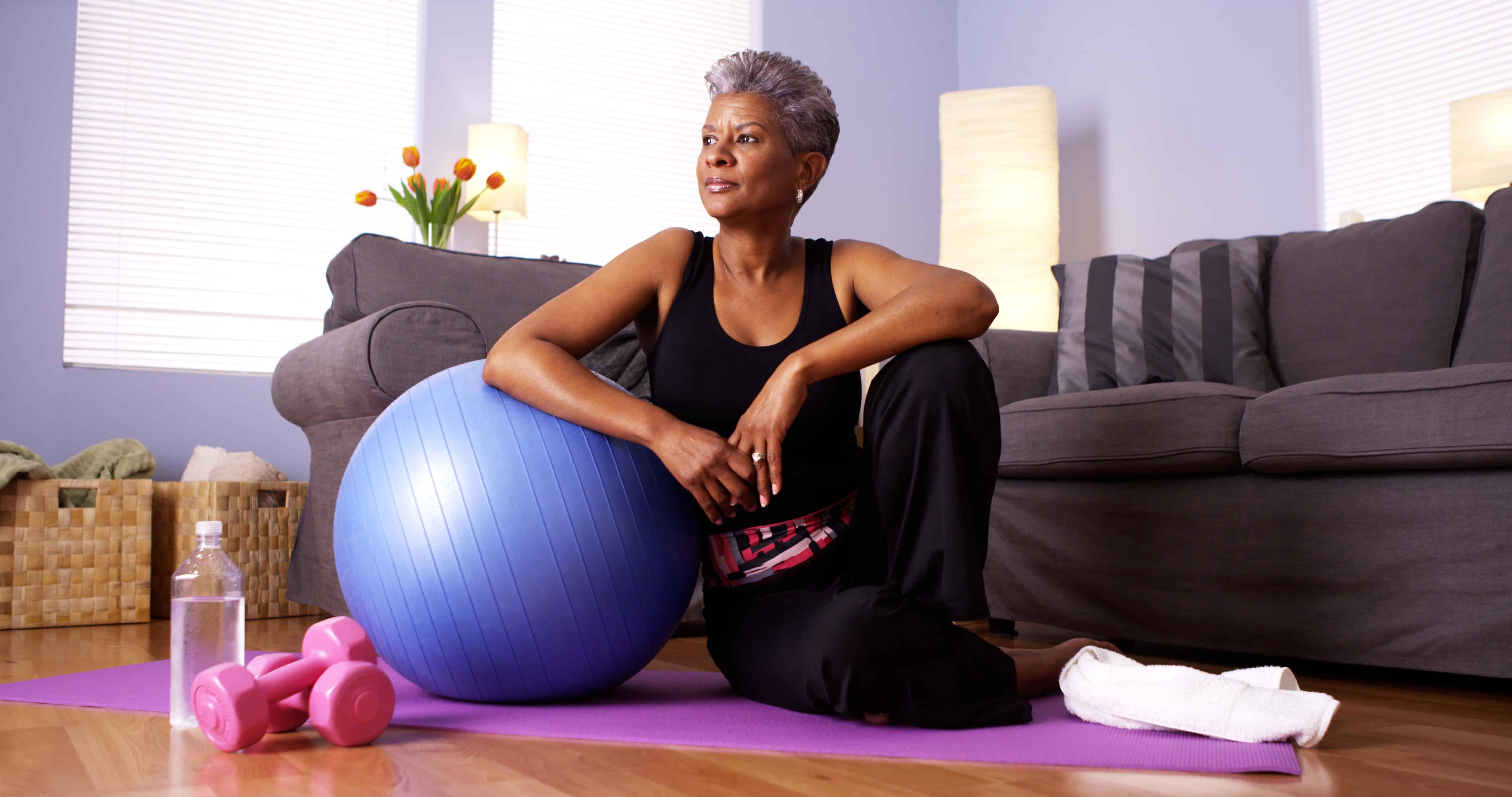 Senior Black woman sitting on floor