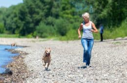 mature woman jogs with a labrador retriever riverside