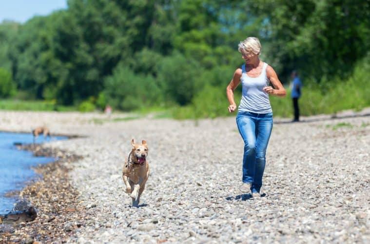 mature woman jogs with a labrador retriever riverside