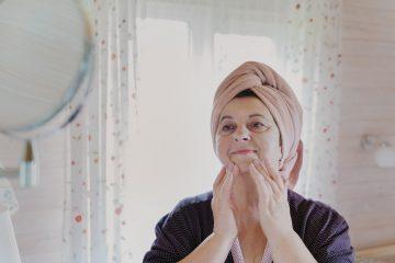 aged-elderly-beutiful-woman-in-bathrobe-and-towel-on-head-applies-cosmetics-cream-does-facial-massage_t20_QKke8k