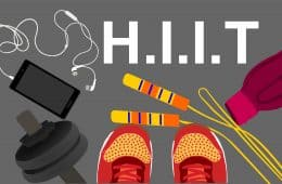 Fitness, healthy and active lifestyles concept. Dumbbells, sport shoes, smart phone,skipping rope with earphone and water bottle on gym floor with word hiit (high intensity interval training)