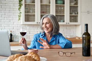 Happy 60s mature woman drinking wine video calling friend on laptop at home.