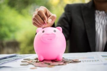 putting coin into a piggy bank on the table finance