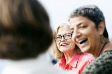 Senior woman talking with female friends outdoors