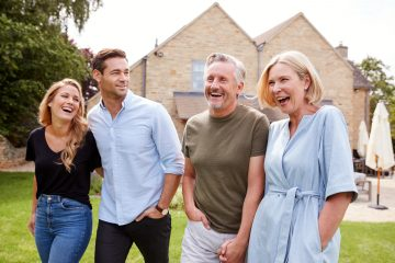 Family With Senior Parents And Adult Offspring Walking And Talking In Garden Together