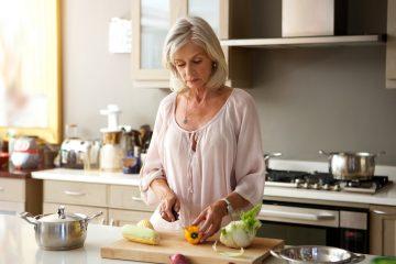 older woman in kitchen preparing healthy meal